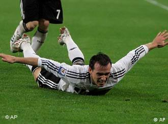 German soccer player laying on grass with arms spread out in celebration