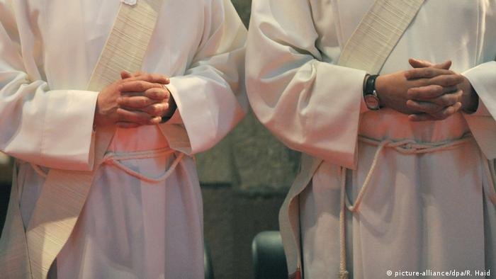 Two Catholic priests standing in white robes