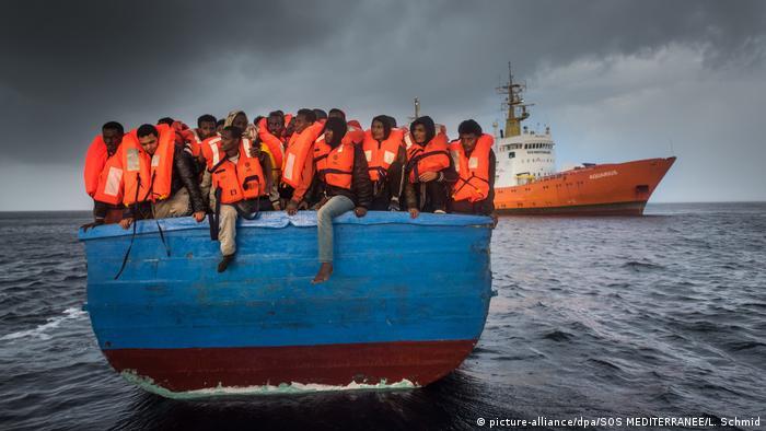 Migrantes são resgatados no Mar Mediterrâneo por uma equipe do navio Aquarius (ao fundo)