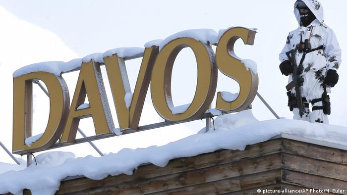 An armed Swiss police officer stands on a roof top during the 'World Economic Forum' in Davos