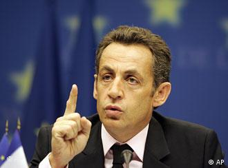 French President Nicolas Sarkozy speaks in front of an EU flag