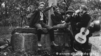 Archivfoto aus 1910 mit vier jungen Männern, die zur Wandervogel-Bewegung gehören. Zwei sitzen auf einer Mauer, einer hat eine Gitarre geschultert.