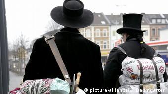 Ein Zimmermann und Zimmerfrau auf Wanderschaft in der für sie tyischen schwarzen Kleidung mit Hut und Bündel.