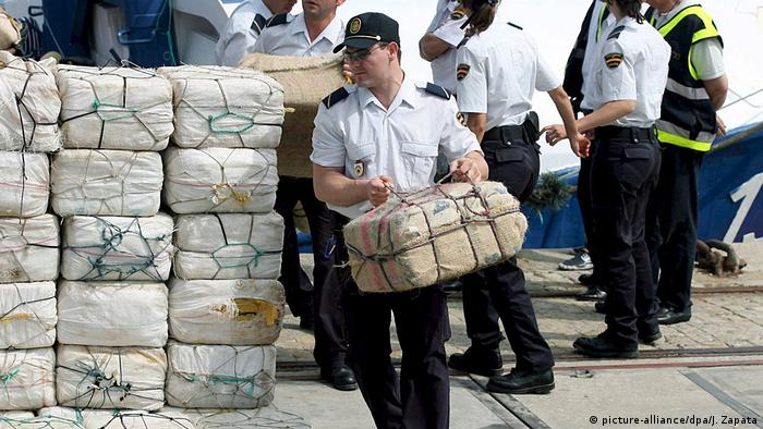 Spanish police carrying parcels containing cocaine found on a fishing boat