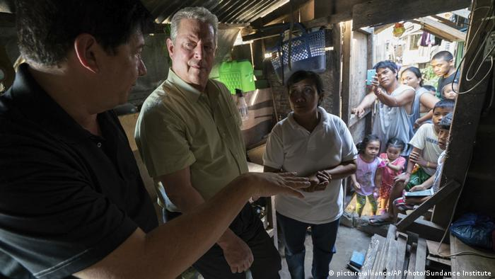 Al Gore stands in a favela and listens to the inhabitants - scene from An Inconvenient Sequel a film by Bonni Cohen and Jon Shenk