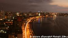 The city lights of the Angolan capital, Luanda, light up the sky, Sunday, Oct. 30, 2005. Three years after the end of civil war, the country is trying to lure foreign tourists to this country where decades of fierce fighting littered the countryside with land mines, left much of it in ruins and decimated the exotic wildlife once abundant in lush national parks. (AP Photo/Obed Zilwa)  