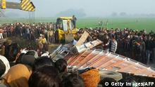 19.01.2017 Indian bystanders gather near the scene of a bus crash in Etah in the state of Uttar Pradesh on January 19, 2017. At least 15 children were killed and dozens more injured when a school bus collided with a truck in northern India on January 19, police said. The driver of the bus also died in the crash, the latest deadly accident in a country with one of the worst road safety records in the world. / AFP / STR (Photo credit should read STR/AFP/Getty Images)