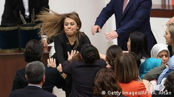 Во время голосования в парламенте одна из депутатов в знак протеста приковала себя наручниками к трибуне, после чего произошла потасовка