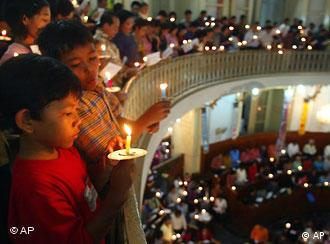 Worshippers hold candle during a Christmas eve mass at a church in Jakarta, Indonesia (AP Photo/Irwin Fedriansyah)
