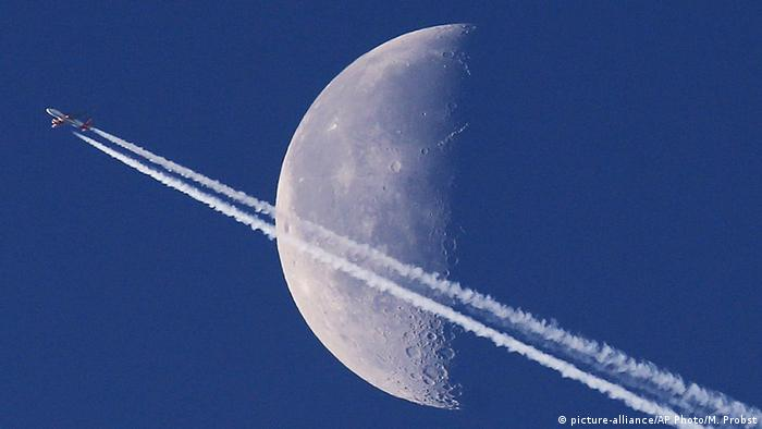 A plane flies past the moon