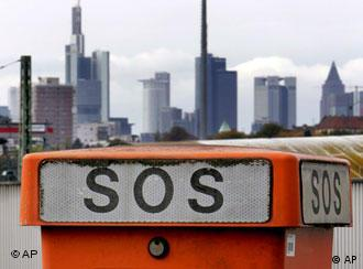 An SOS phone booth sits in front of Frankfurt's skyline
