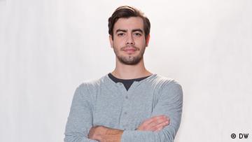 Portrait von Nico. Er hat braunes Haar, helle Haut, braune Augen und einen Drei-Tage-Bart. Er ist schlank und groß.