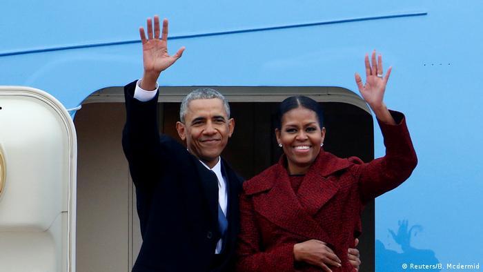 Barack Obama e Michelle Obama acenam na porta de um avião