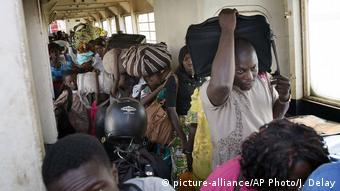 People wait to disembark from a ferry arriving at the port in Banjul