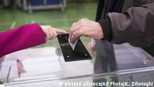 Voters drop their votes into a ballot box in France
