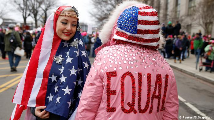 A woman wearing a US flag headscarf gazes at another wearing a pink parka emblazoned with 'Equality' and a US flag hood (Reuters/S.Stapleton)