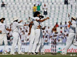 Indian cricket players run-in to congratulate bowler Ishant Sharma, fourth left, after he took the wicket of Australian captain Ricky Ponting, unseen, on the second day of the second cricket test match between India and Australia in Mohali, India, Saturday, Oct. 18, 2008. (AP Photo/Gautam Singh)