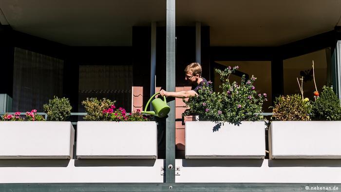 Молодой человек поливает цветы на балконе