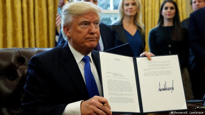 President Donald Trump holds up a signed executive order to advance construction of the Keystone XL pipeline at the White House in Washington. Photo credit: Reuters/K. Lamarque.