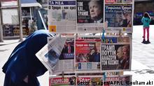 A woman passes newspapers featuring headlines with reactions following Donald Trump's shock US presidential victory in Athens on November 10, 2016. A triumphant Donald Trump heads to the White House Thursday for talks with President Barack Obama on securing a smooth transition of power and steading nerves after an election that shocked the world. / AFP / LOUISA GOULIAMAKI (Photo credit should read LOUISA GOULIAMAKI/AFP/Getty Images)