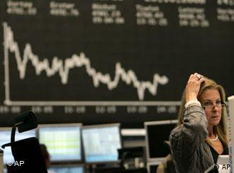A trader grabs her head at the Frankfurt stock exchange