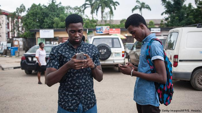Two young men in Nigeria look at their mobile phones while standing in a carpark