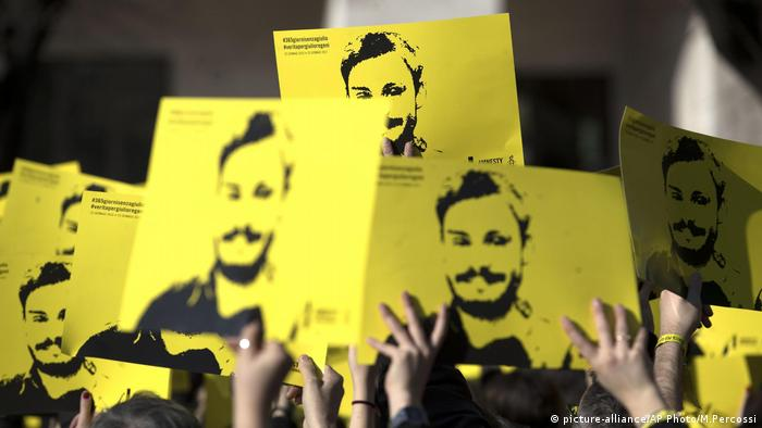 People hold up pictures of Giulio Regeni and reading in Italian ''365 days without Giulio Regeni (picture-alliance/AP Photo/M.Percossi)