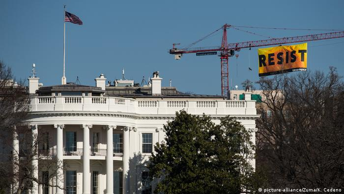 Greenpeace activists unfurl a banner reading 'Resist' from atop a construction crane behind the White House