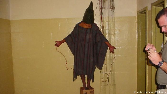 A detainee stands on a box with a bag on his head and wires attached to him at Abu Ghraib prison in Iraq