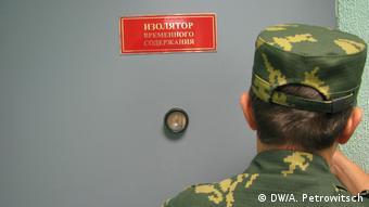 Пограничник перед дверью с табличкой Изолятор временного содержания