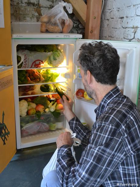 A man looks inside his fridge. Photo credit: Foodsharing.