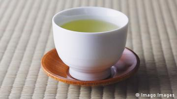 A white cup with green tea on a brown saucer.