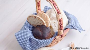 A bread basket with several types of bread.