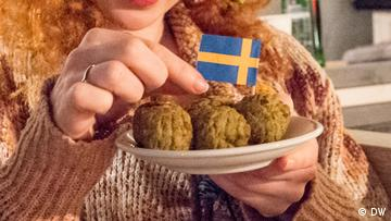 Close-up of Swedish meatballs on a plate with a little Swedish flag.