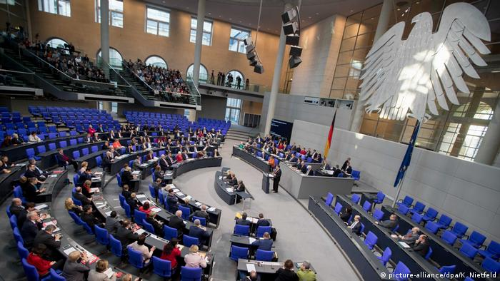 German representatives fill the blue chairs of the Bundestag which forms a crescent facing the stand from which speakers address the lower house. Onlookers fill the gallery above the seats. A large, silver eagle hangs on the far wall of the Bundestag