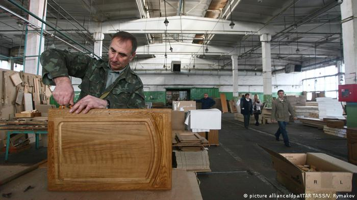 Рабочий в цеху мебельной фабрики собирает шкаф