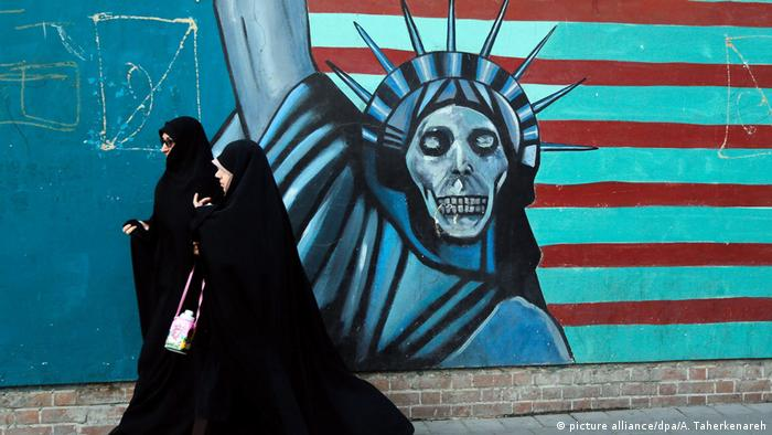 Iranian women pass next to an anti-US mural (picture alliance/dpa/A. Taherkenareh)