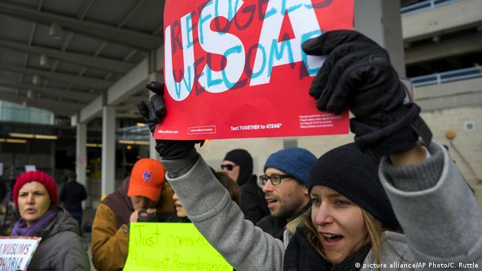 Женщина в международном аэропорту имени Джона Кеннеди в Нью-Йорке держит плакат в поддержку приема беженцев.