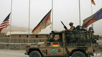 German tank as part of NATO's ISAF troop deployment in Afghanistan with US, German and Russian flags fluttering in background