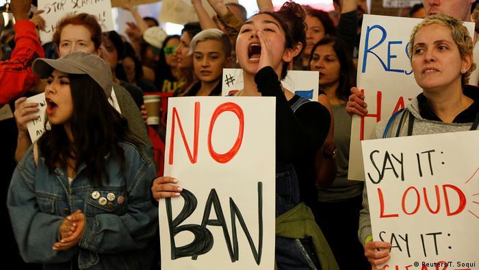 Protestors hold signs at LAX airport