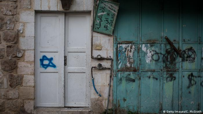 A Star of David is seen painted on the door of a house next to a shuttered Palestinian shop on a street that separates an Israeli settlement and a Palestinian neighborhood in Hebron