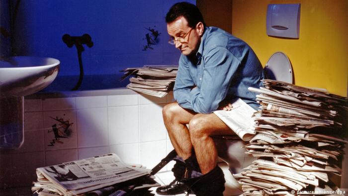 Pessoa sentada em vaso sanitário, cheia de jornais em volta