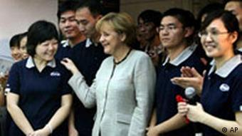 German Chancellor Angela Merkel greets Chinese workers during her visit to the Daimler auto factory in Beijing