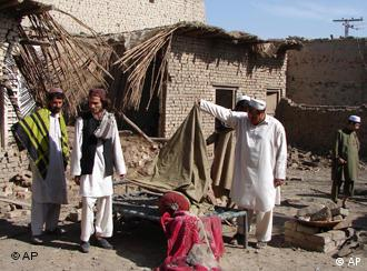 Pashtoon tribesmen look at belongings in a house that they said was hit by a U.S. missile strike in Pakistan