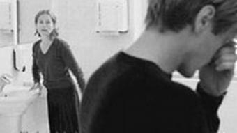 Szene aus Die Klavierspielerin im Hintergrund Isabelle Huppert, vorne Mann in Rückenansicht (Filmverleih)