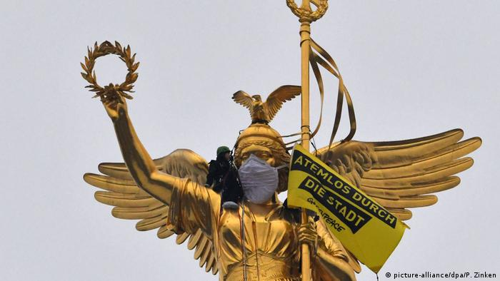 Activists hang a particle filter mask over the Victory Column in Berlin