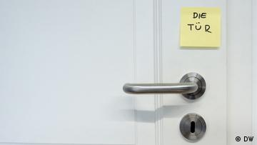 Detail of a door handle with a note stuck to it, Text 'die Tür'