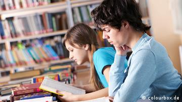 A boy and a girl sitting in a library reading