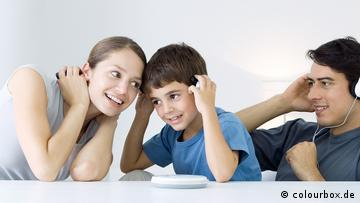 A young woman, a child and a young man all wearing headphones