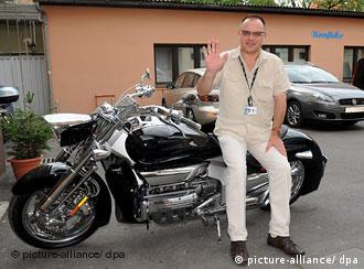 Ivo Pukanic leaning against his motorcycle in a parking lot
